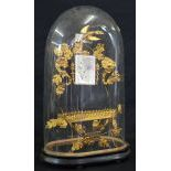 Gilded filigree, wreath and flower ornaments of metal underneath a glass globe on wooden stand. With...